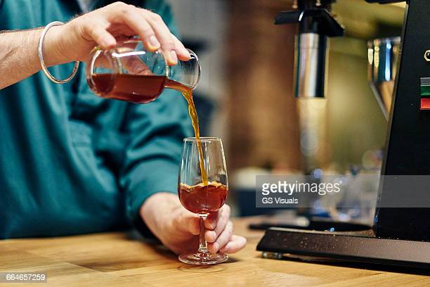 Hands of male barista pouring cold brew coffee into wine glass on coffee shop counter