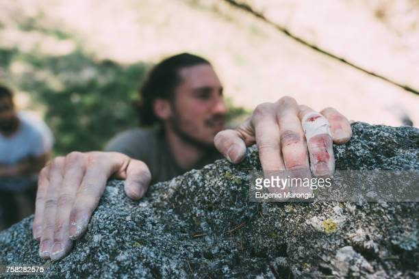 Hands of male boulderer gripping boulder edge, Lombardy, Italy