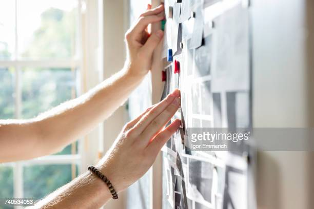 hands of male designer pinning mood board ideas to wall in creative studio - design professional stock pictures, royalty-free photos & images