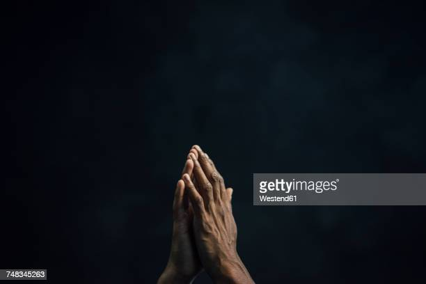 hands of man and black background - religion stock-fotos und bilder