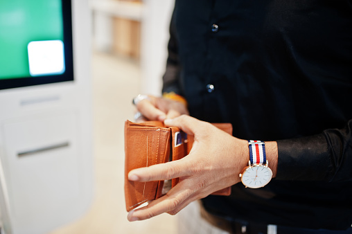 Hands of man customer at store place orders and pay through self pay floor kiosk for fast food, payment terminal. His holding wallet and find credit card. 1128206820