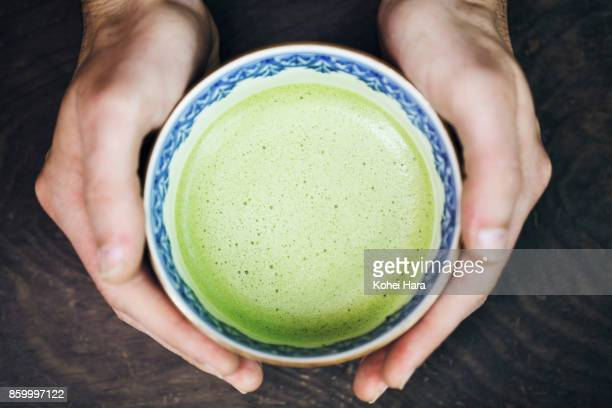 Hands of man holding a cup of Japanese powdered green tea