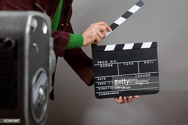 hände von mann hält filmklappe vor alten altmodischen kamera - filmregisseur stock-fotos und bilder