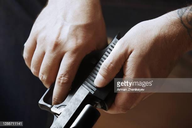 hands of man holding handgun - gun barrel stock pictures, royalty-free photos & images