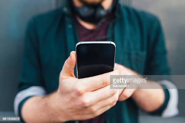 Hands of man holding smartphone, close-up