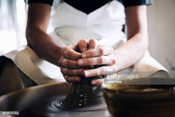 Hands of man making ceramic work with potter's wheel