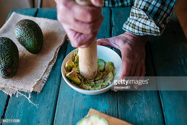 Hands of man mashing avocado for guacamole