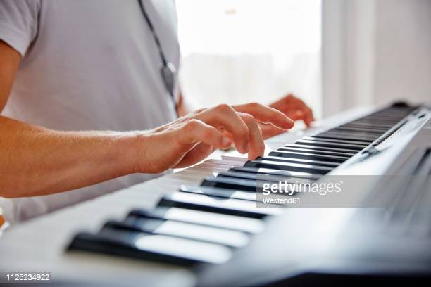 hands of man playing digital piano - electric piano stock photos and pictures