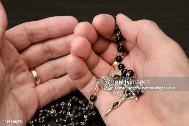 hands of man praying the rosary with black beads and crucifix with mary our lady of fatima - fatima portugal photos et images de collection