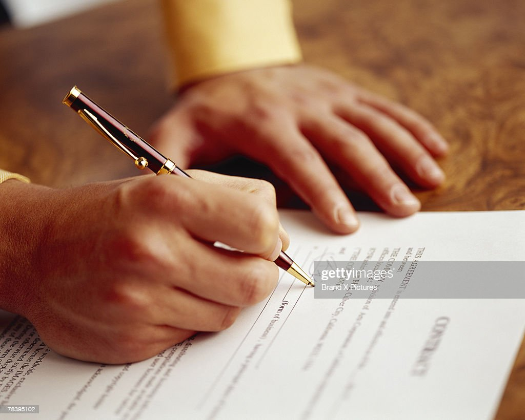 Hands of man signing contract : Stock Photo