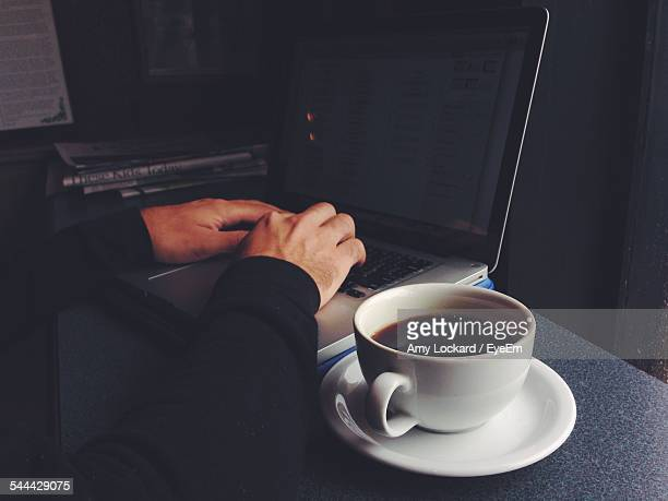 Hands Of Man Using Laptop And Cup Of Coffee