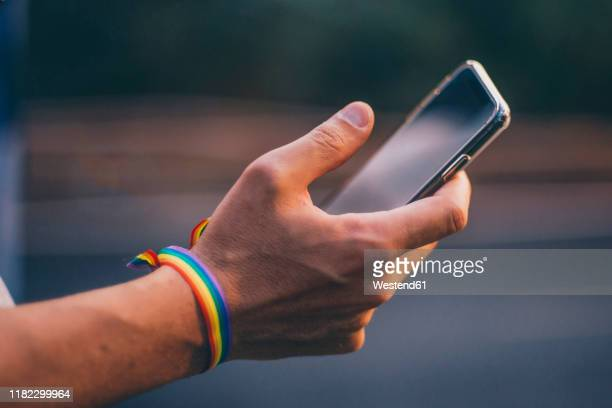 hands of man with pusera gay flag holding an smartphone - thumb stock pictures, royalty-free photos & images