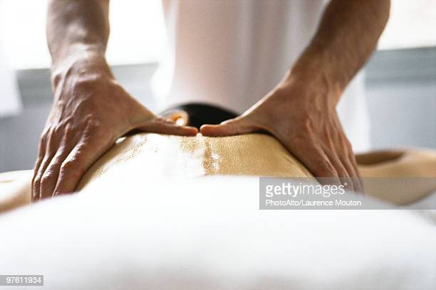 Hands of massage therapist massaging woman's back
