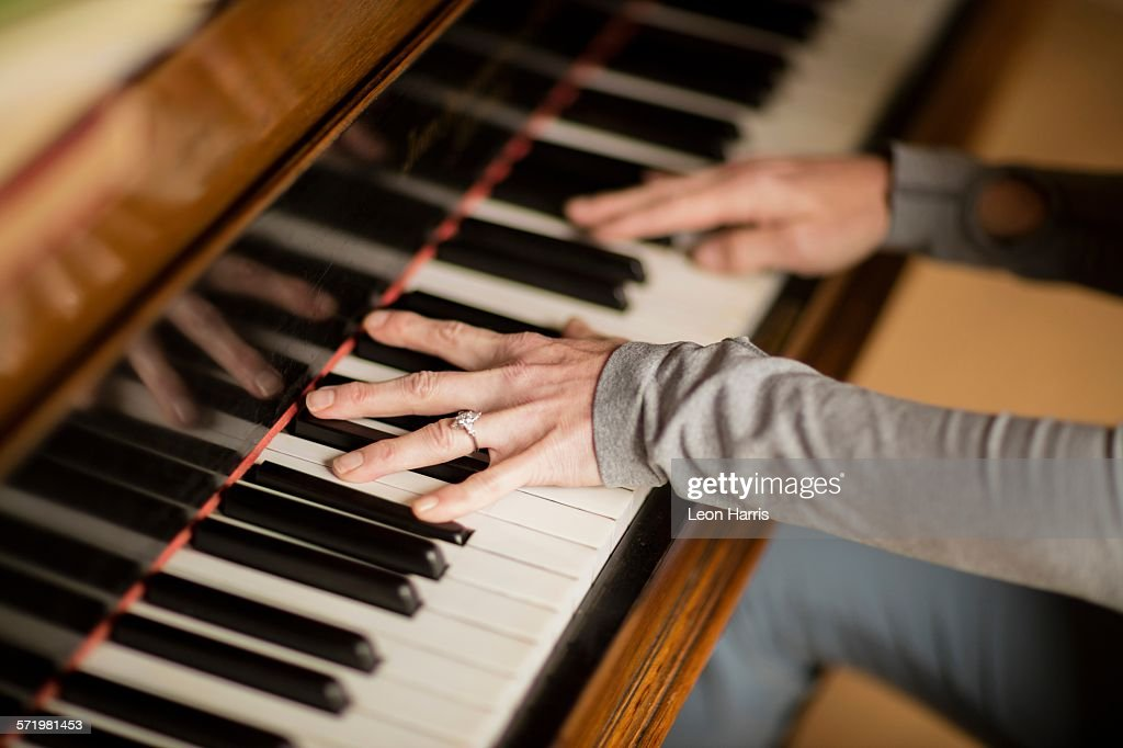 Hands of mature woman playing piano : Stock Photo