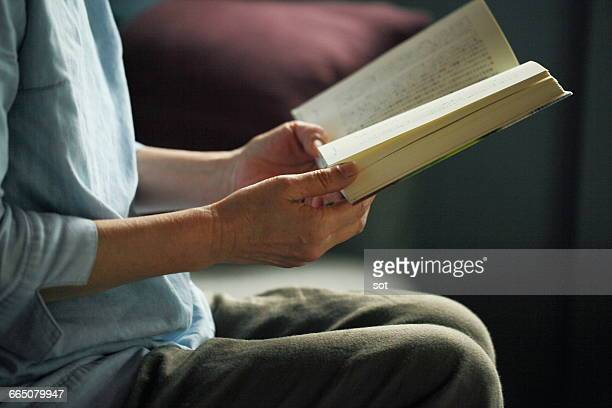 Hands of mature woman reading book,close up