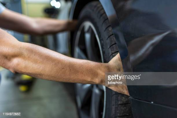 hands of mechanic changing a wheel of a modern car - wheel stock pictures, royalty-free photos & images