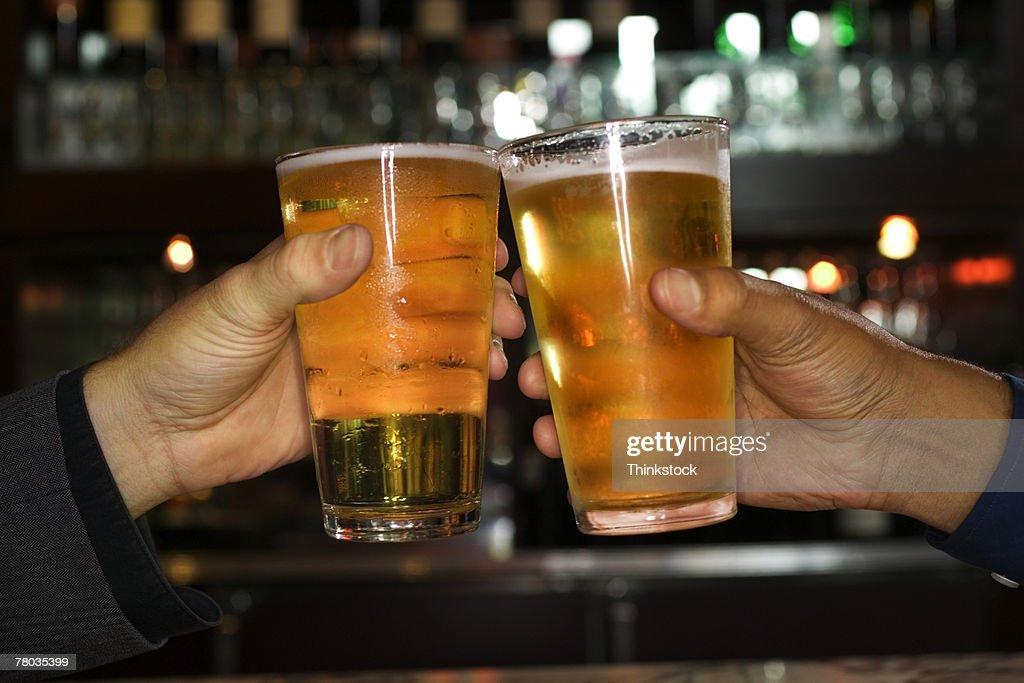 Hands of men toasting with beer : Stock Photo