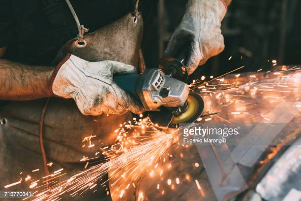 Hands of metalworker grinding copper in forge workshop