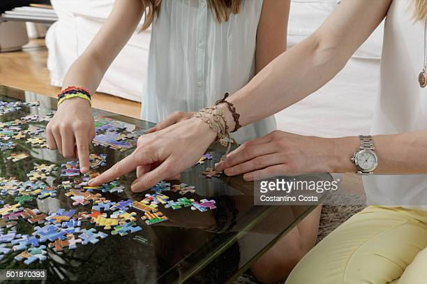 Hands of mother and daughter doing jigsaw puzzle
