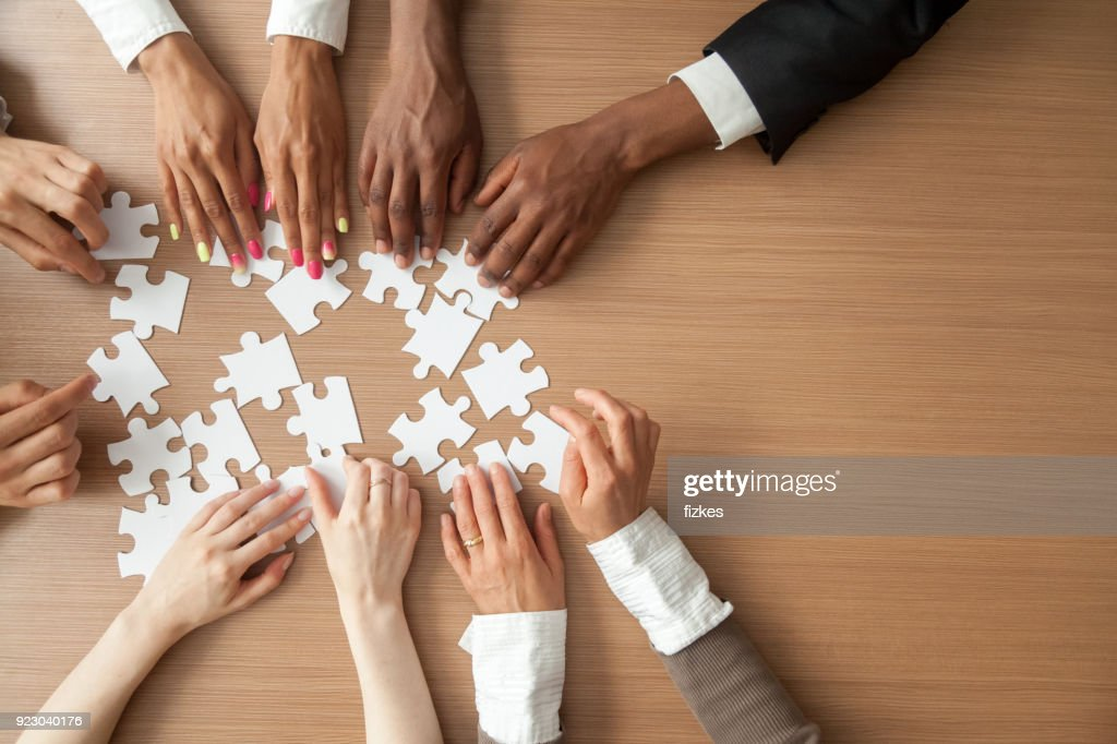 Hands of multi-ethnic business team assembling jigsaw puzzle, top view : Foto de stock