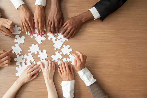 Hands of multi-ethnic business team assembling jigsaw puzzle, top view 923040176
