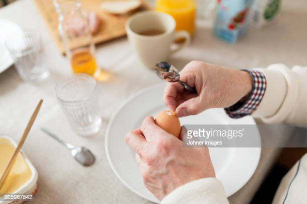 Hands of older person peeling egg at breakfast table