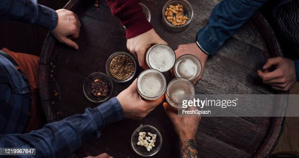 hands of people toasting with beer at a pub - honour stock pictures, royalty-free photos & images
