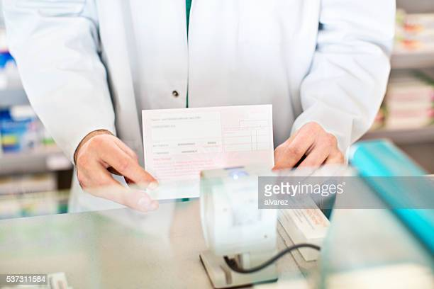 Hands of pharmacist checking out customer's medication prescription