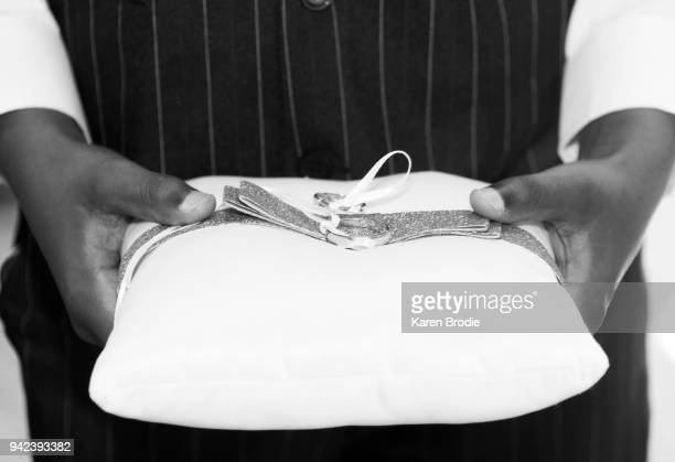 Hands of ring bearer carrying pillow with wedding rings attached