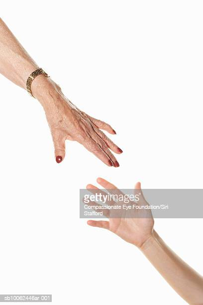 Hands of senior and mid adult woman reaching out towards each other, close-up