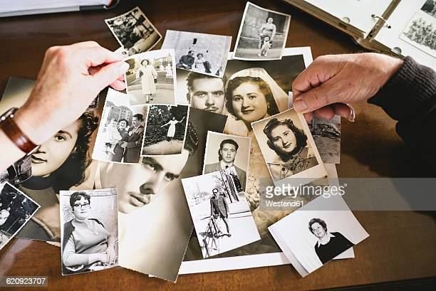 hands of senior couple holding old photographies of themselves - photo album stock photos and pictures