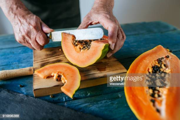 hands of senior man cutting papaya - papaya stock photos and pictures