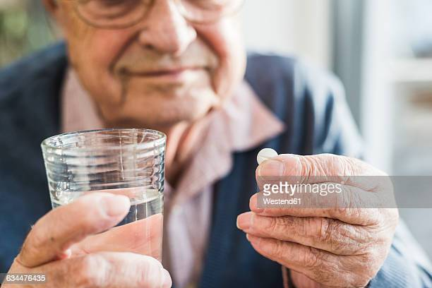 hands of senior man holding tablet and glass of water, close up - taking a pill stock pictures, royalty-free photos & images