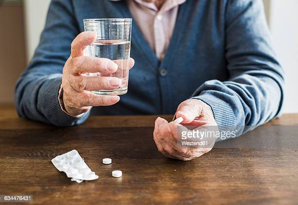 Hands of senior man holding tablet and glass of water, close-up