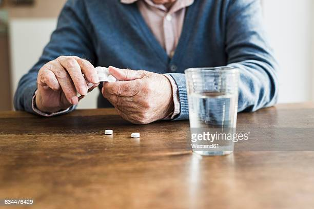 Hands of senior man taking tablets out of blister pack, close-up