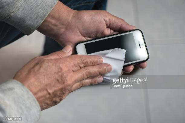 hands of senior spanish man cleaning his mobile phone with a cloth - dorte fjalland stock pictures, royalty-free photos & images