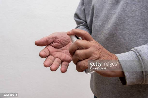 hands of senior spanish man spraying his hands with rubbing alcohol - dorte fjalland stock pictures, royalty-free photos & images
