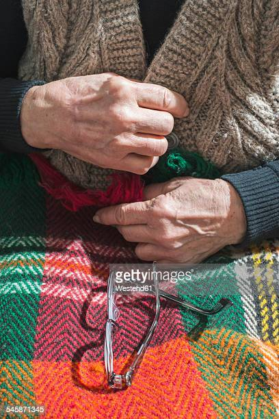 Hands of senior woman buttoning her vest while glasses lying on blanket