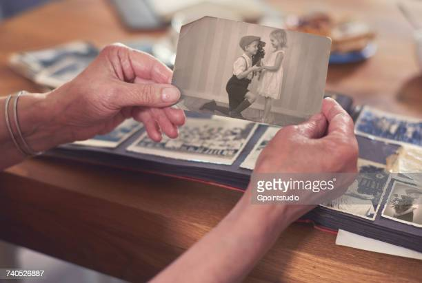 Hands of senior woman holding old photograph of boy and girl