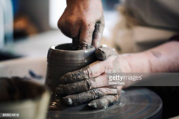 Hands of senior woman making ceramic work with potter's wheel