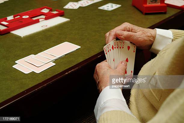 Hands of senior woman Playing Cards