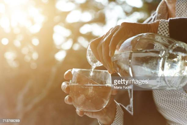 hands of senior woman pouring glass of water by window - fülle stock-fotos und bilder
