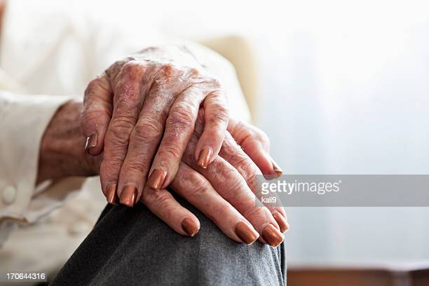 Hands of senior woman resting on her knee