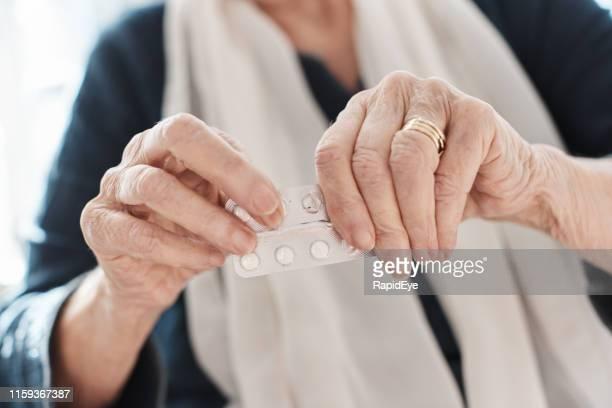 handen van senior vrouw worstelt om pakket van tabletten te openen - medicijnen innemen stockfoto's en -beelden