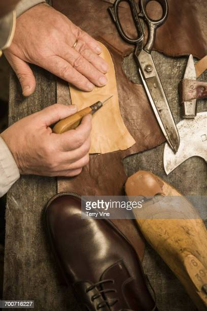 hands of shoemaker using awl on leather - calzature di pelle foto e immagini stock