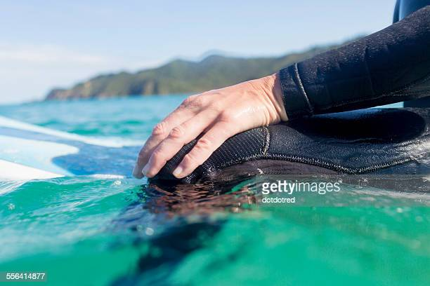 Hands of surfer in the water, Bay of Islands, NZ