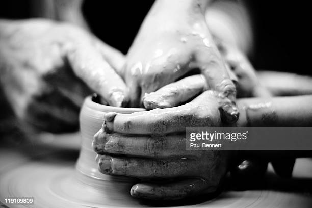 Hands of teacher and child in pottery class