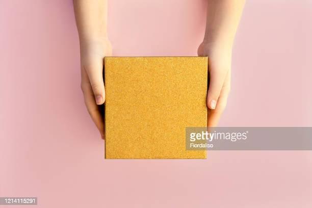 hands of teenage girl holding a golden gift box on pink background - gift hand stock-fotos und bilder