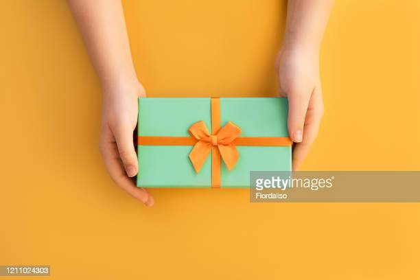 hands of teenage girl holding a green gift box with a yellow satin ribbon on red background - 贈り物 ストックフォトと画像
