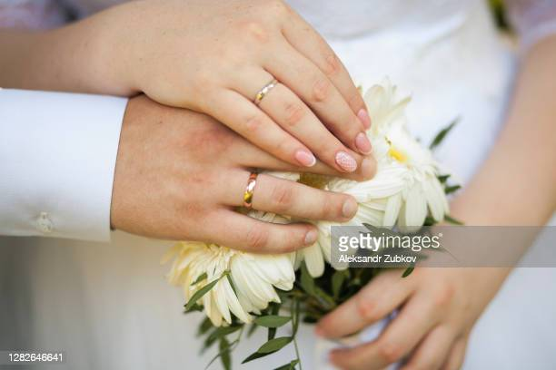 hands of the bride and groom on a beautiful wedding bouquet with pink and white flowers, green leaves. newlyweds on their wedding day. - married stock pictures, royalty-free photos & images